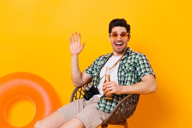 Charmante man in groen geruit overhemd zwaait met zijn hand, lachen, flesje bier en retro camera op oranje ruimte te houden.