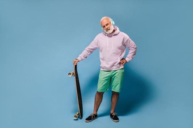 Charmante man in hoodie en groene korte broek die naar muziek luistert en een skateboard vasthoudt