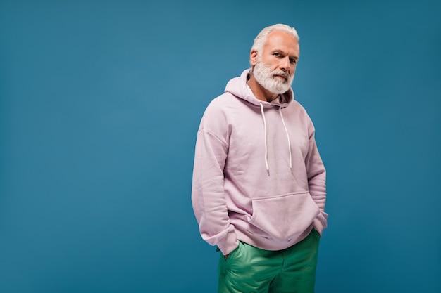 Charmante man in witte hoodie op zoek naar camera op blauwe muur
