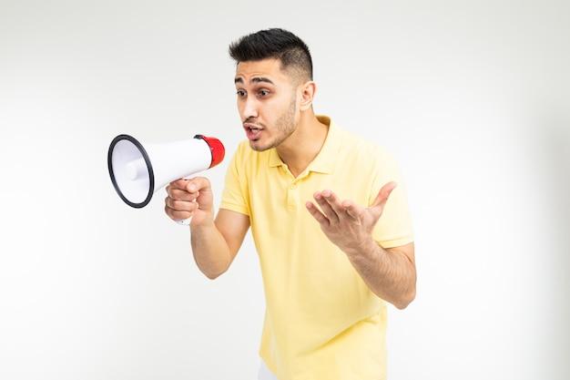 Charmante man met een megafoon in zijn handen schreeuwt het nieuws over kortingen voor aankopen op een witte achtergrond