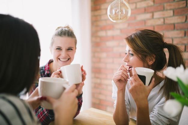 Charmante meisjes die tijdens het praten met nieuws delen