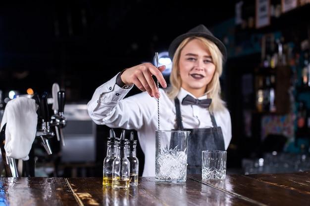 Charmante meisjesbarman maakt een show en creëert een cocktail achter de bar