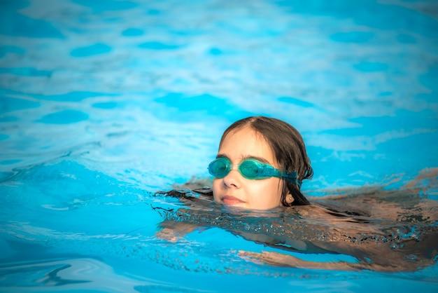 Charmante meisjestiener met een waterdichte bril voor het zwembad zwemt in het heldere, warme en blauwe water tijdens de zomervakantie. concept van fysieke activiteit voor kinderen. advertentie ruimte