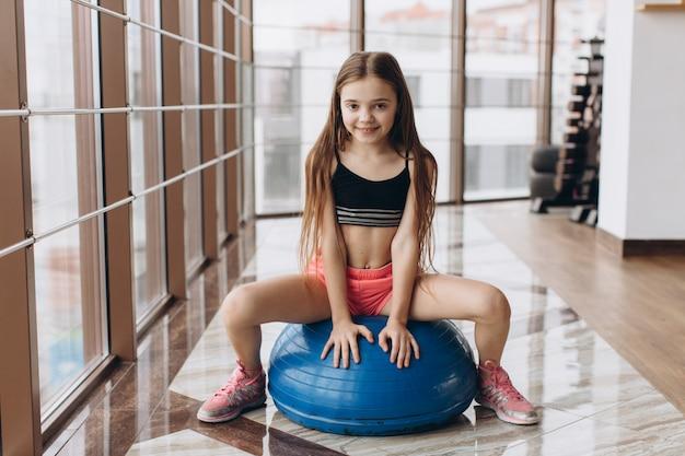 Charmante meisjezitting op bal in geschiktheidszaal