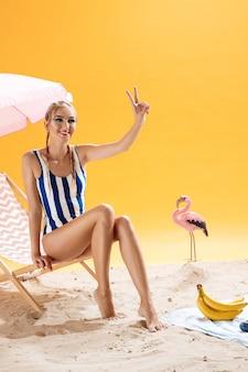 Charmante modelvrouw op strand die vredesteken tonen die weg eruit zien