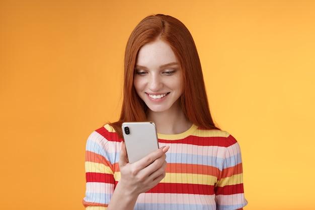 Charmante moderne roodharige studente die een berichtvenster controleert met een smartphone, een blij lachend, opgetogen mobiel display, ontvangt honderd likes fotopost online, oranje achtergrond.