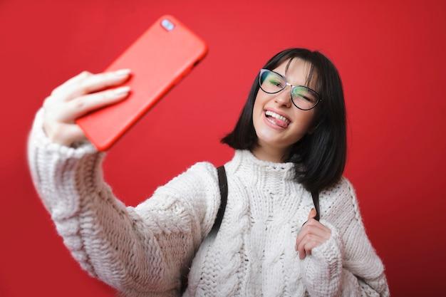 Charmante moderne vrouw in trui en bril selfie te nemen en tong te tonen op rode achtergrond