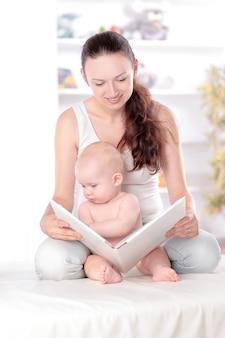 Charmante moeder die een boek voorleest aan haar baby.concept van onderwijs