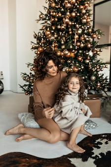 Charmante moeder en dochter met krullend kapsel hebben plezier, knuffel en kus thuis in de buurt van de kerstboom in een wit interieur