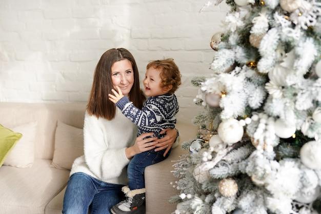 Charmante moeder in de witte sweater die haar zoontje peuter in de buurt van de kerstboom in huis houdt