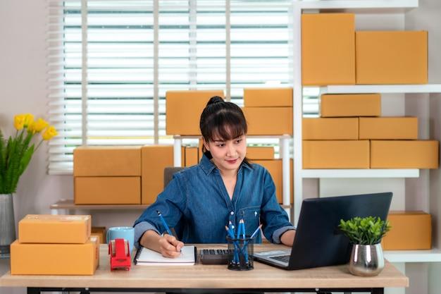 Charmante mooie aziatische tiener eigenaar zakenvrouw werken thuis voor online winkelen, op zoek naar de volgorde in laptop en notitie in haar boek met kantoorapparatuur, ondernemer lifestyle concept