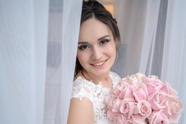 Charmante mooie bruid bij het raam met een bruiloft boeket van roze rozen in de ochtend