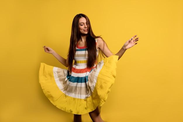 Charmante mooie dame met lang donker haar, gekleed in gestripte zomerkleding dansen.