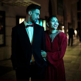 Charmante mooie glimlachende dame die met jonge kerel op straat loopt