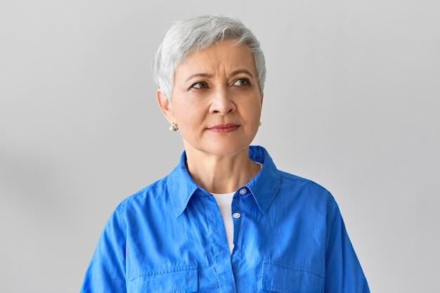 Charmante mooie grijze vrouw van middelbare leeftijd bij pensionering poseren geïsoleerd tegen een lege muur met copyspace voor uw tekst of reclame-inhoud, bedachtzaam glimlachend