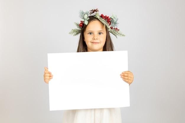 Charmante mooie meisjes in de kroon van kerstmis met witte lege banner geïsoleerd op een witte achtergrond...