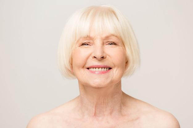 Charmante, mooie, oude vrouw met perfecte zachte huid, glimlachend in de camera op witte achtergrond, met dag, nacht gezichtscrème, cosmetische procedures