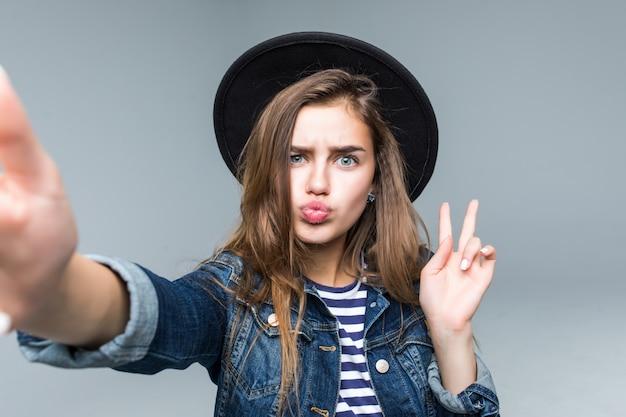 Charmante mooie vrouw met vredesgebaar in zwarte hoed en zonnebril nemen selfie uit handen op grijze achtergrond