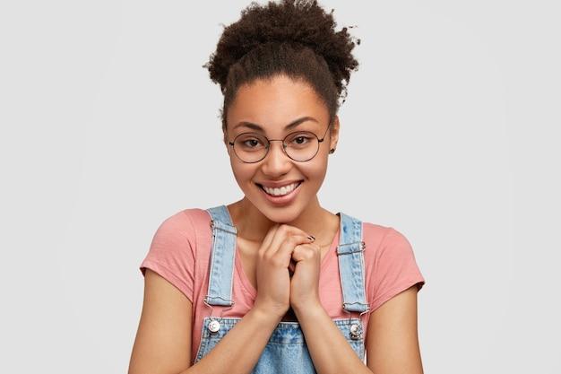 Charmante mooie vrouw met vriendelijke glimlach, werkt in café, blij om bezoekers te ontmoeten, houdt handen bij elkaar, verdient haar brood, draagt casual t-shirt met overall, geïsoleerd over witte muur.