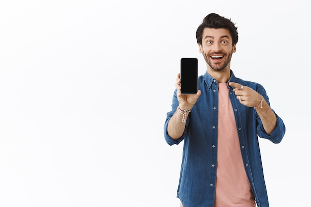 Charmante onder de indruk, glimlachende gelukkige man met baard, smartphone vasthoudend, iets op een leeg scherm latend, wijzend display en verbaasde grijns, goede app aanbevelen, weggevertje, witte muur