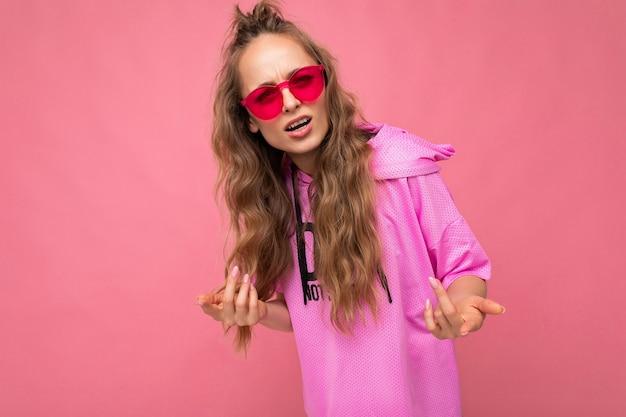 Charmante ontevreden overstuur jonge blonde krullende vrouw geïsoleerd op roze achtergrond muur dragen casual