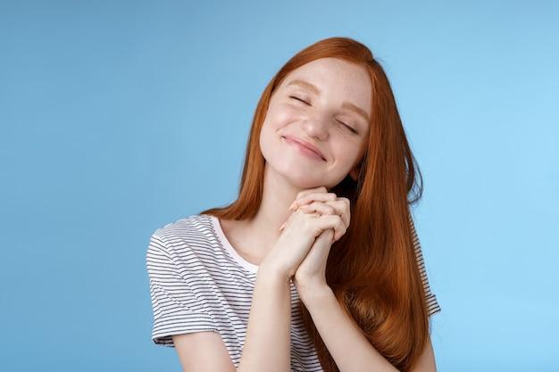 Charmante opgetogen blije dromerige roodharige vriendin gember lang haar kantelend hoofd ogen sluiten glimlachend blij dagdromen denkend aan zoete tedere herinneringen druk de handpalmen tegen elkaar, blauwe achtergrond.
