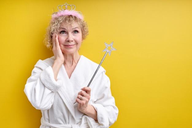 Charmante oudere vrouw in badjas met kroon op het hoofd, magische toverstaf in handen, senior fee, verrast gezicht wangen aanraken
