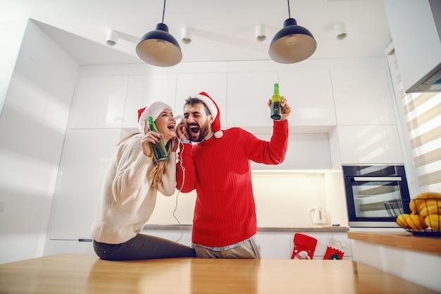 Charmante paar met kerstmutsen op hoofden muziek luisteren via een koptelefoon en zingen
