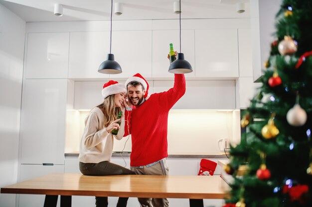 Charmante paar met santa hoeden op hoofden muziek luisteren via een koptelefoon
