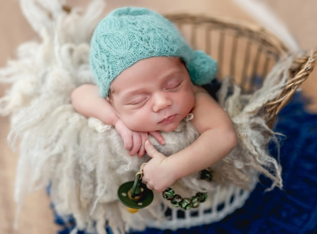 Charmante pasgeboren babyjongen slapen in mand met een fopspeen in de hand