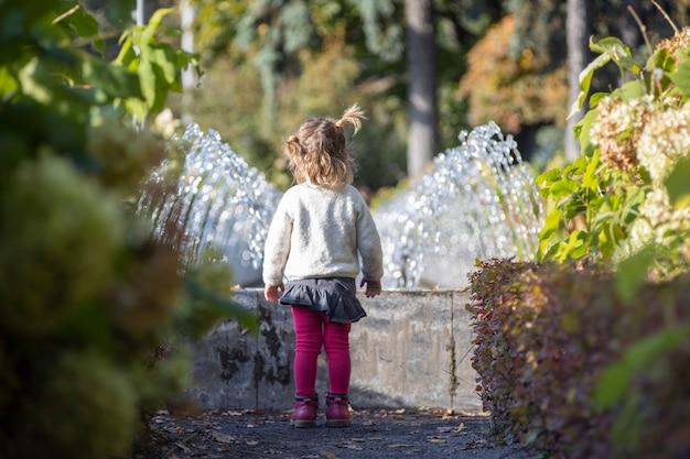 Charmante peuter in het park met fonteinen op de achtergrond. zomerdag