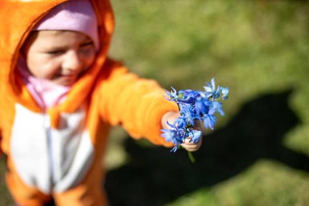 Charmante peuter met lentebloemen buiten in zonlicht