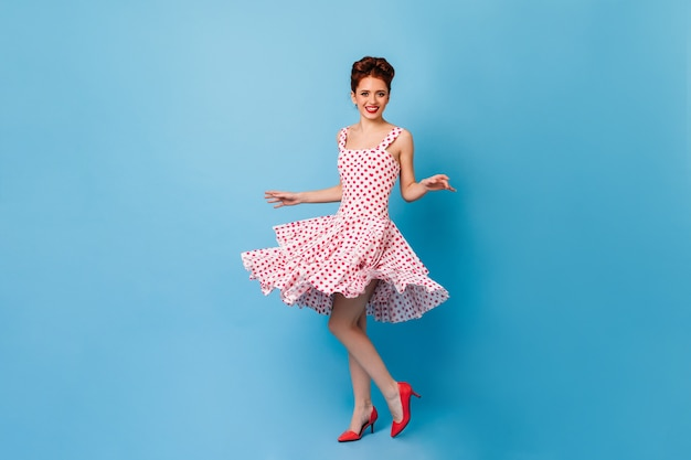 Charmante pinupvrouw die camera met oprechte glimlach bekijkt. studio shot van vrouwelijk model in polka-dot jurk dansen op blauwe ruimte.