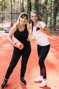 Charmante plus size vrouw met haar vriendin kijken camera lachen na het doen van hun ochtendsport buiten in een sportpark.