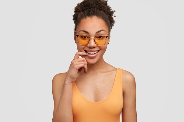 Charmante positieve afro-amerikaanse vrouw heeft brede glimlach, gezonde donkere huid, houdt wijsvinger dichtbij tanden