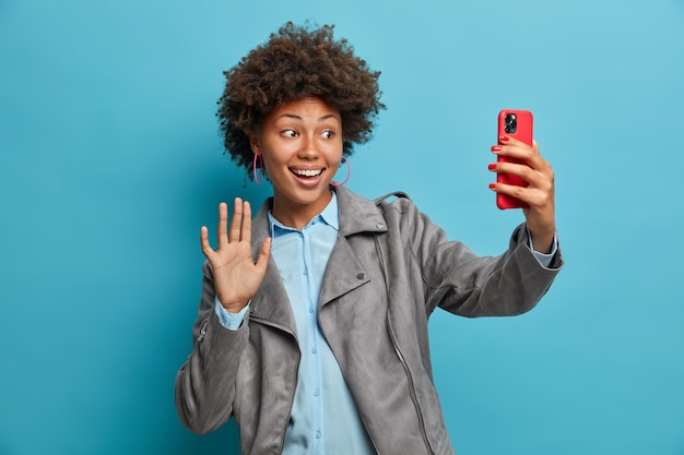 Charmante positieve donkere huid vriendelijke vrouw geniet van informele bijeenkomst online, zwaait met de palm en zegt hallo in smartphone, gebruikt video-messanger, neemt selfie, draagt stijlvolle grijze jas, begroet vriend