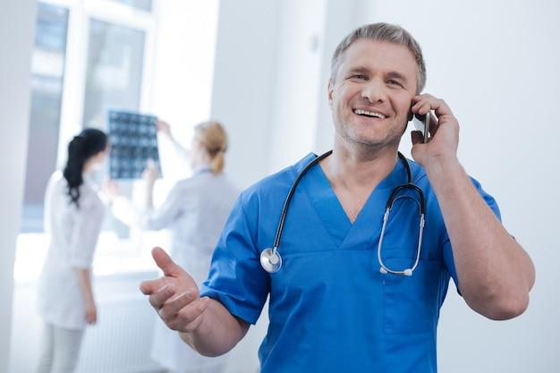 Charmante positieve knappe radiologische technoloog die in het medisch laboratorium werkt en geniet van een gesprek aan de telefoon terwijl andere artsen x-ray foto achter onderzoeken