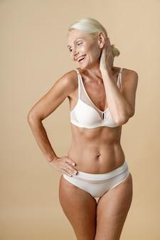 Charmante rijpe vrouw in ondergoed met een perfect lichaam dat lacht en haar hoofd aanraakt