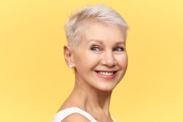 Charmante rijpe vrouw met pixie blond haar wegkijken met blije glimlach, poseren geïsoleerd tegen gele achtergrond met kopie ruimte voor uw tekst