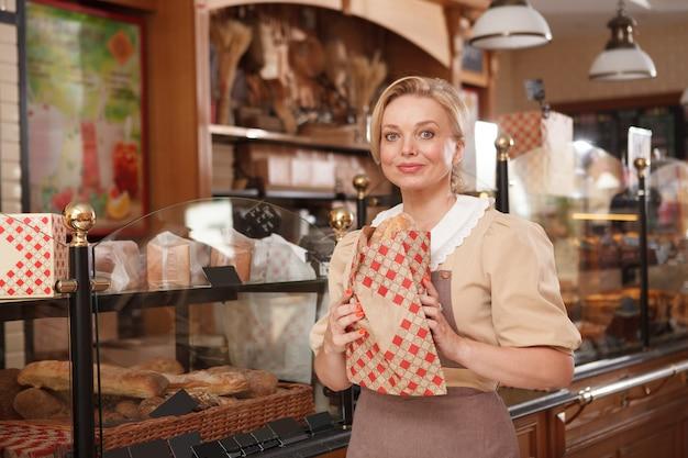 Charmante rijpe vrouwelijke bakker die graag in haar bakkerij werkt