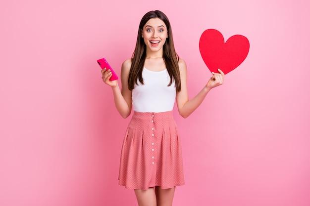 Charmante romantische brunette dame houd rode papieren hartkaart vast telefoon vast