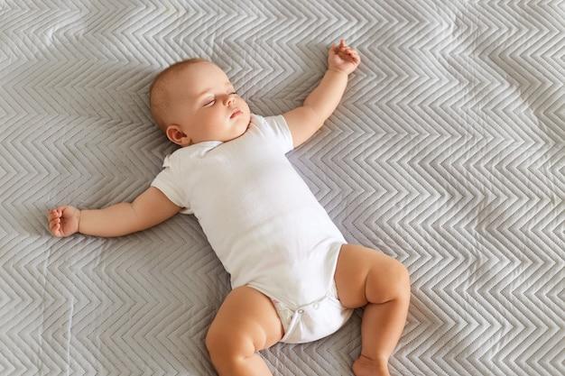 Charmante schattige baby liggend op een bed, slapend in een lichte kamer op grijze deken, liggend met spreidende handen, middagslaap binnen.