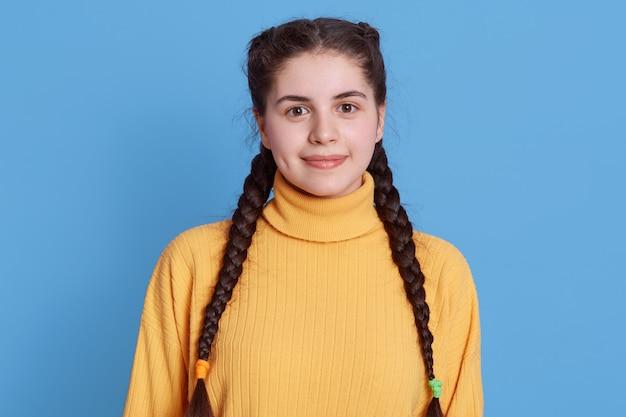 Charmante schattige glimlachende vrouw met donker haar en vlechten, gekleed in gele casual trui, direct kijkend, poseren geïsoleerd over blauwe muur