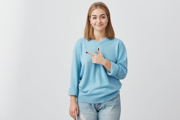 Charmante schattige jonge europese vrouwelijke klant glimlachend en wijsvinger zijwaarts wijzend, met lege witte muur met kopie ruimte voor uw promotionele inhoud