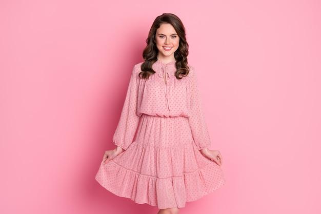 Charmante schattige verlegen droomdame die zich voordeed op roze muur