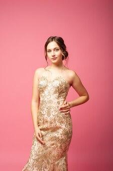 Charmante schattige vrouw met avondkapsel en in glanzende beige jurk poses met handen op taille ...