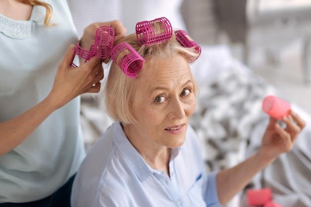 Charmante senior vrouw die naar de voorkant kijkt en een roze haarroller vasthoudt, terwijl haar dochter haar helpt om er nog meer vast te maken