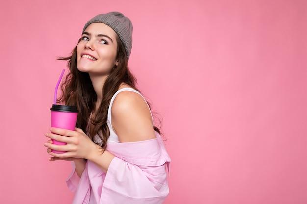 Charmante sexy jonge gelukkig grappige brunette vrouw draagt stijlvolle kleding geïsoleerd over kleurrijke achtergrond muur met papieren beker voor mockup milkshake drinken op zoek naar de kant. kopieer ruimte