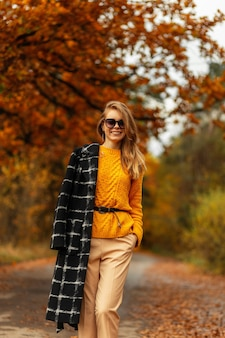 Charmante sexy jonge vrouw in modieuze sportkleding met stijlvolle roze rugzak loopt op bossen bij zonsondergang. mooi blond meisje wandelen in het park en geniet van zonlicht op zomerdag. gezonde levensstijl.