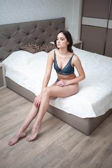Charmante sexy vrouw in lingerie liggend op het bed in de kamer